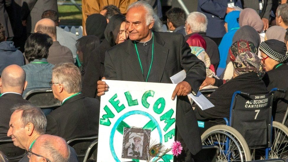 """A man holding a sign saying """"welcome"""" for the family members of victims of the Christchurch mosque shootings"""