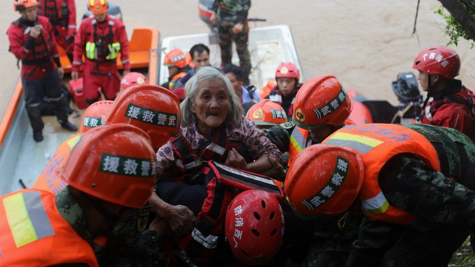 Police officers evacuate trapped people from a flood-hit area in southern China
