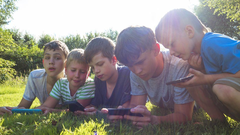 Children of varied ages looking at screens outdoors