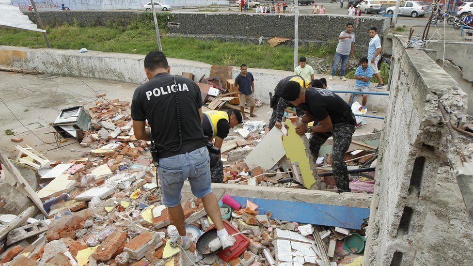 Police sift through debris in Manta, Ecuador, after a massive earthquake