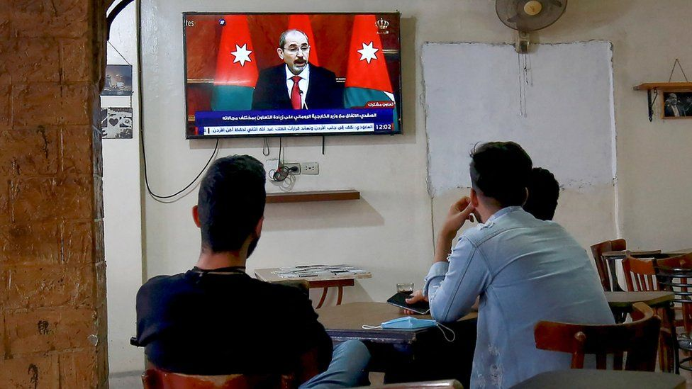 Jordanians follow the latest political developments in their country on a television set at a cafe in the capital Amman