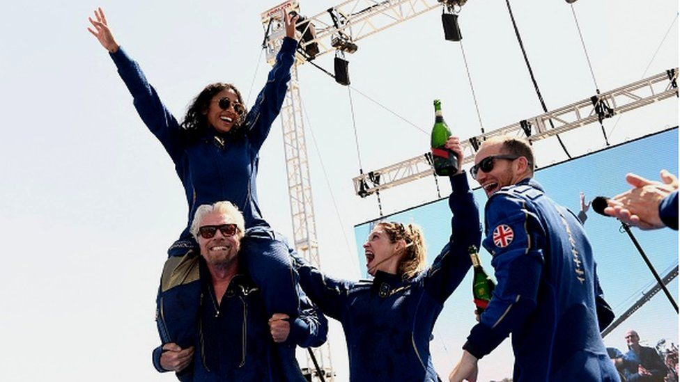 Sir Richard Branson celebrates with the crew of Virgin Galactic with Sirisha Bandla perched on his shoulder