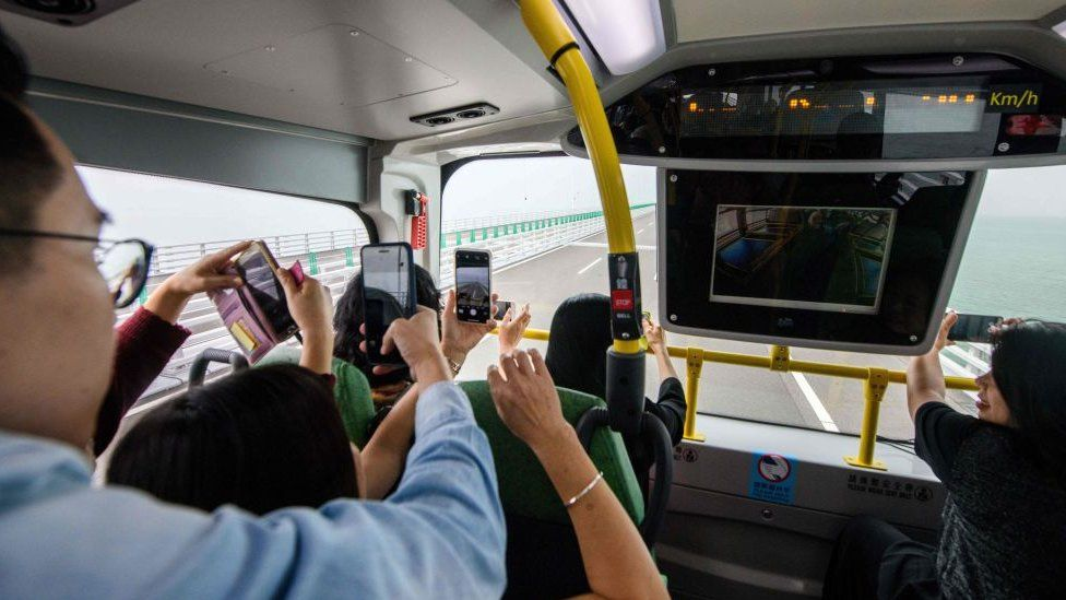 Passengers take photos in a bus being driven towards Macau