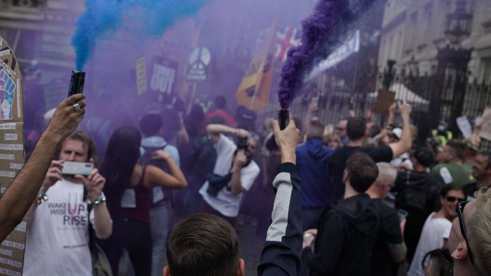 Protesters let off flares outside Downing Street during an anti-lockdown protest in central London.