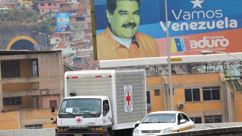 A billboard depicting Venezuela's President Nicolas Maduro is seen in the background as trucks marked with the logo of the International Federation of Red Cross and Red Crescent Societies (IFRC) and believed to be carrying humanitarian aid, drive on a highway in Caracas, Venezuela, April 16, 2019