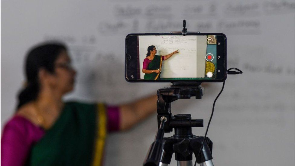 A school teacher gives a live streaming online class at a government school
