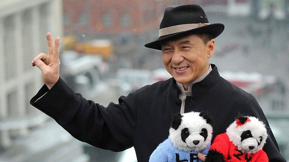Hong Kong action film star Jackie Chan holds toy pandas as he poses for photos atop a hotel roof just outside the Kremlin in Moscow