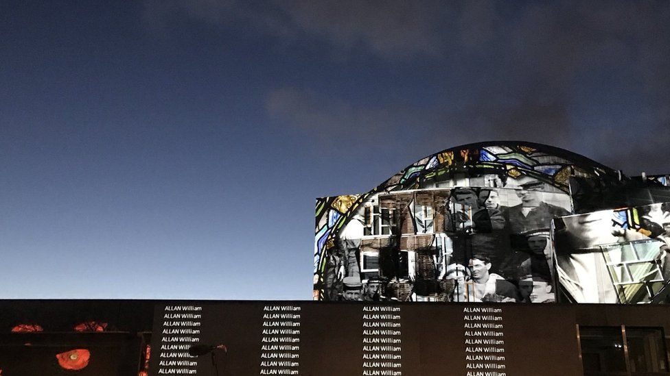 Names and photos projected on to the side of the Scottish Parliament building.