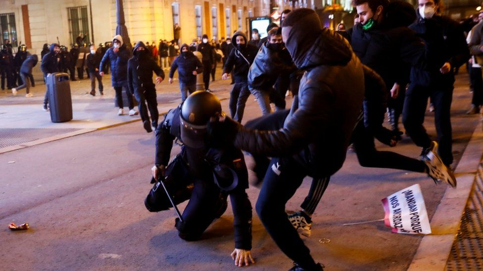 Demonstrators kick a police officer as supporters of Catalan rapper Pablo Hasél protest against his arrest in Madrid, Spain