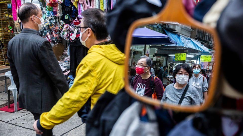 Las personas que usan máscaras protectoras caminan por un mercado en Hong Kong