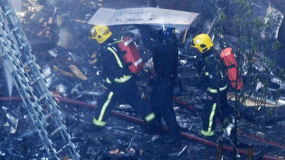 Emergency services walking through debris