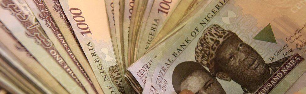 man holds handful of 1,000 naira banknotes