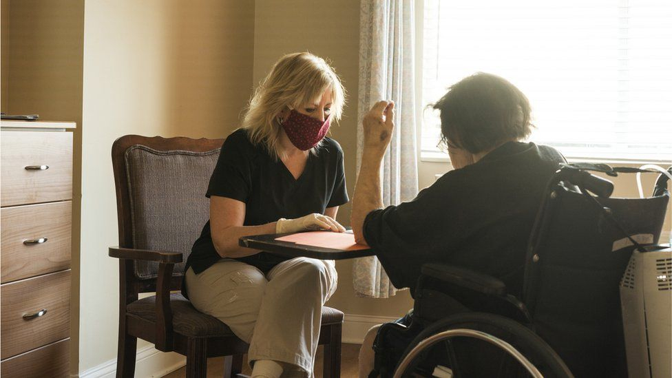 A care home worker with a resident