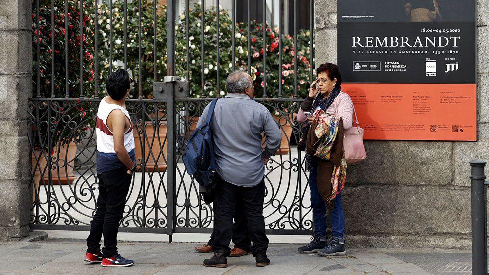 People look at closed doors of Prado museum in Madrid - 12 March