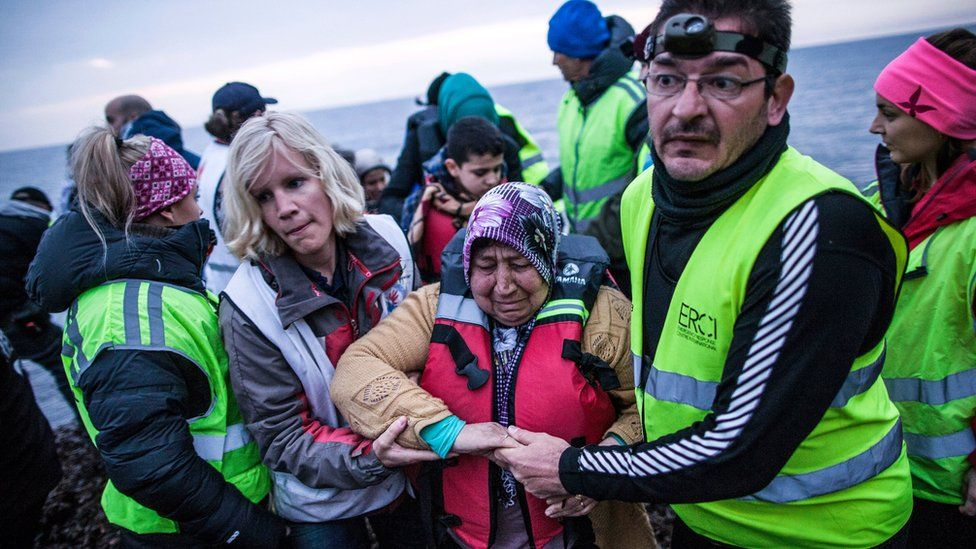 A Syrian woman is helped by volunteers after her arrival with other refugees and migrants on a dinghy from the Turkish coast to Mytilene, Lesbos island, Greece, Friday, Feb. 26, 2016
