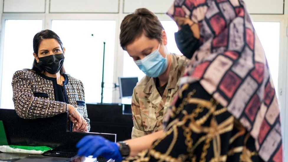 Priti Patel watches an Afghan refugee give her fingerprints during processing at Heathrow