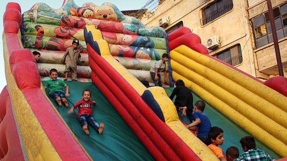 Children playing on a bouncy slide in Tabqa in 2015