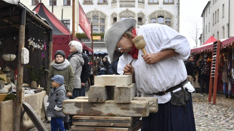 A traditional wood cutter engraves wood in the main square in Wittenberg, eastern Germany, where celebrations take place on the occasion of the 500th anniversary of the Reformation on October 31, 2017