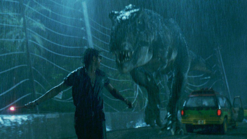 A scene from the film Jurassic Park - a man runs from a tyrannosaurus rex in the rain