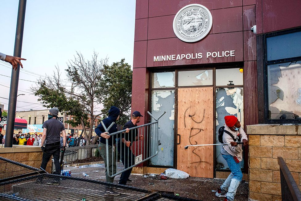 Protesters use a barricade to try and break the windows of the 3rd Police Precinct