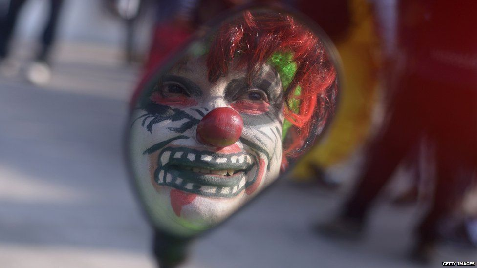 A clown's reflection in a mirror