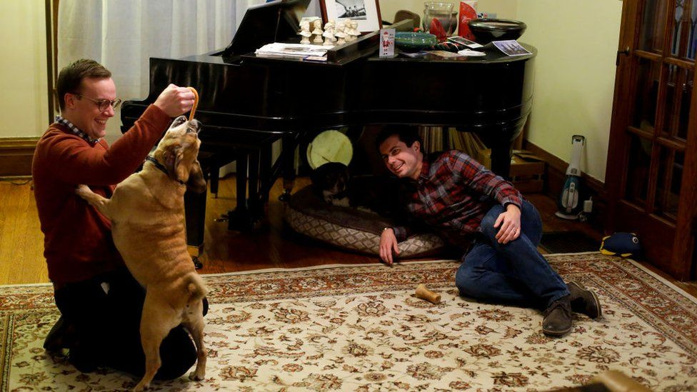Mr Buttigieg with his husband Chasten Glezman and their dog Buddy at their Indiana home