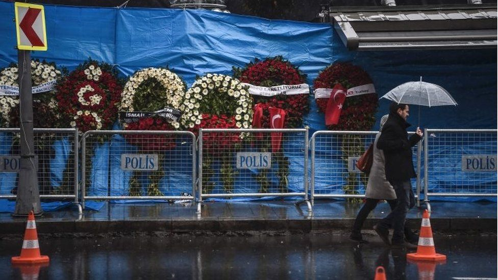 A couple walk past the Reina nightclub on 5 January 2017 in Istanbul, days after a gunman killed 39 people on New Year's night.