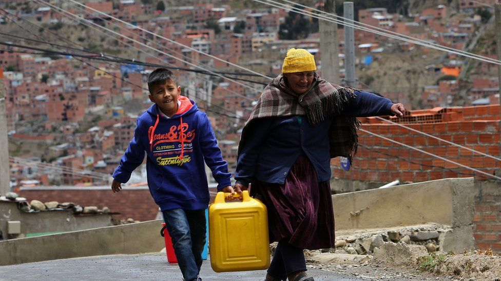 A woman and a child carry a bucket of water collected from a truck provided by officials of the Bolivian public water company, 22 November 2011