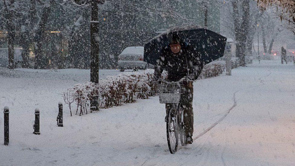 man rides his bike under heavy snow in the city centre of Ljubljana, Slovenia (13 January 2017)