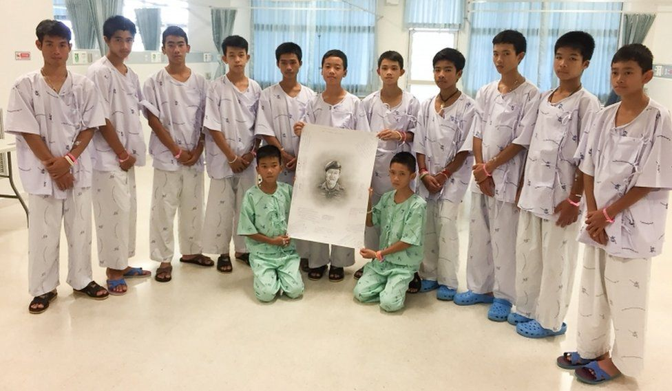 """The 12-member """"Wild Boars"""" soccer team and their coach rescued from a flooded cave pose with a drawing picture of Samarn Gunan, a former Thai navy diver who died working to rescue them, at Chiang Rai Prachanukroh Hospital"""