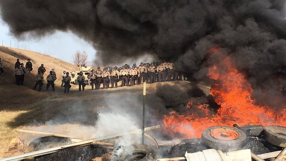 Tires burn as armed soldiers and law enforcement officers stand in formation on Thursday, Oct. 27, 2016, to force Dakota Access pipeline protesters off private land where they had camped to block construction.