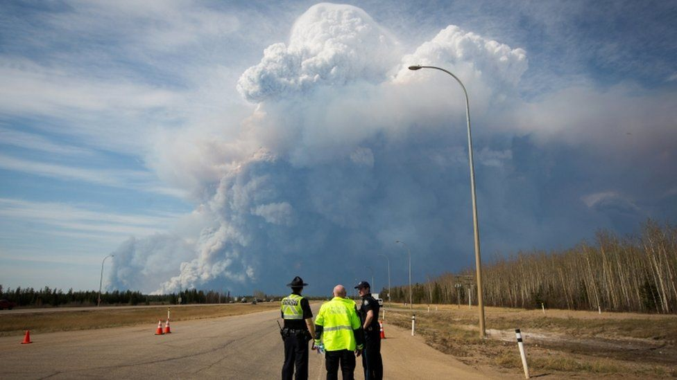 Police officers look as smoke billows from a wildfire in Fort McMurray, Canada. Photo: 4 May 2016