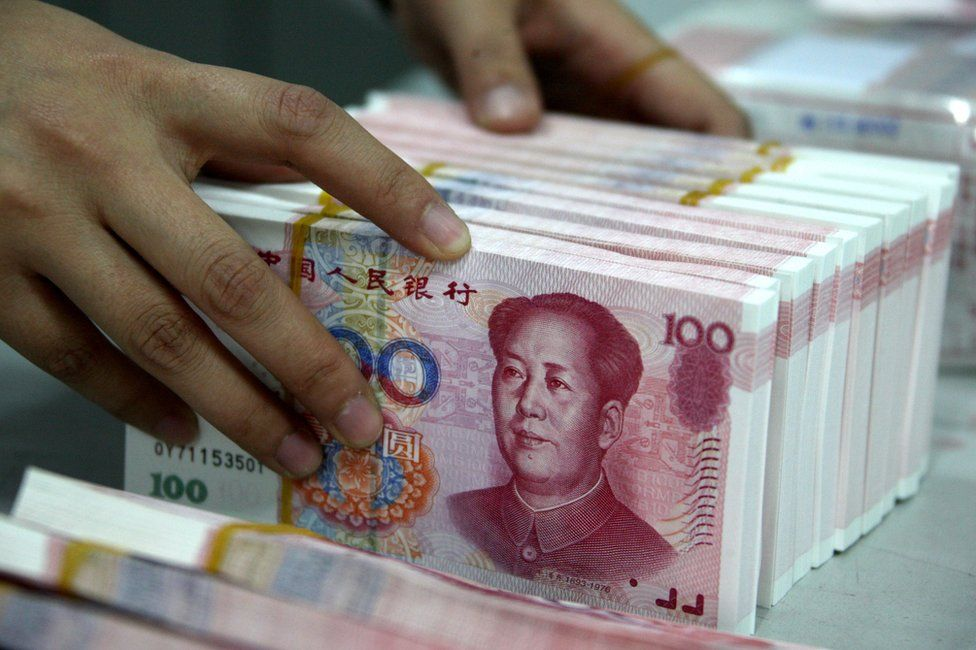 Chinese bank teller counts stacks of Chinese 100-yuan (one hundred yuan) notes at a bank in Huaibei, east China's Anhui province on 12 November 2010