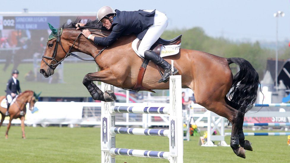 A showjumper and horse jump a fence at Balmoral Show