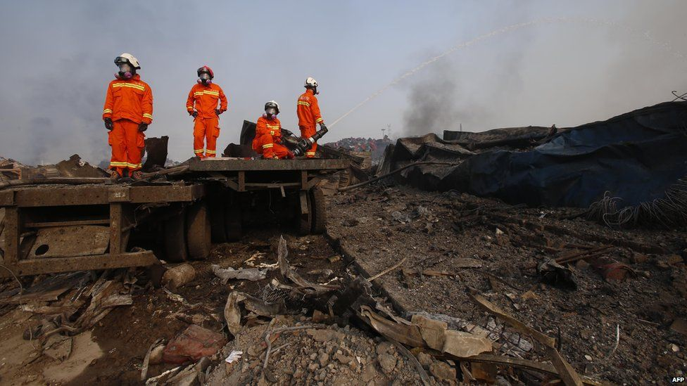 Firefighters work at the site of the explosions