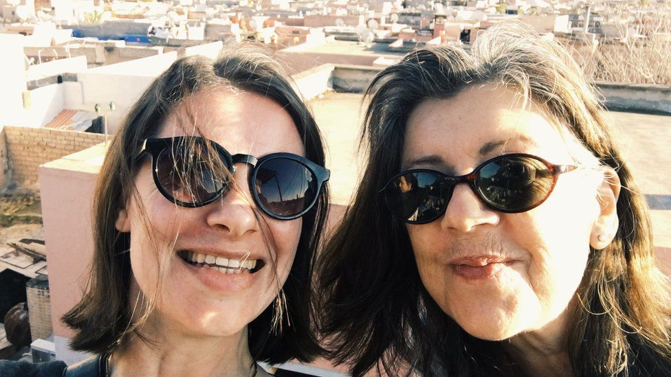 Two women in sunglasses on a rooftop in Morocco