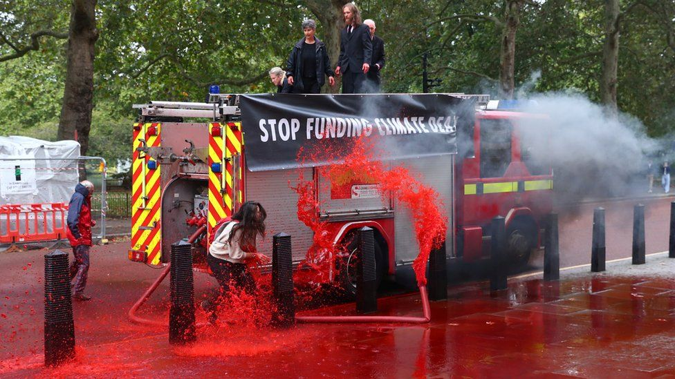 Extinction Rebellion protesters spray red water at the Treasury