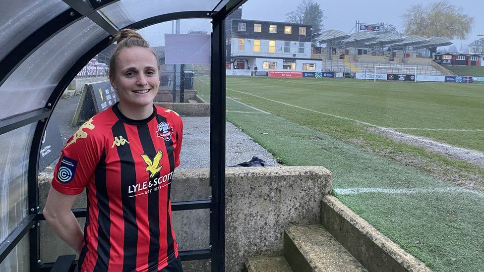 Sarah Kempton standing in the dugout at Lewes FC