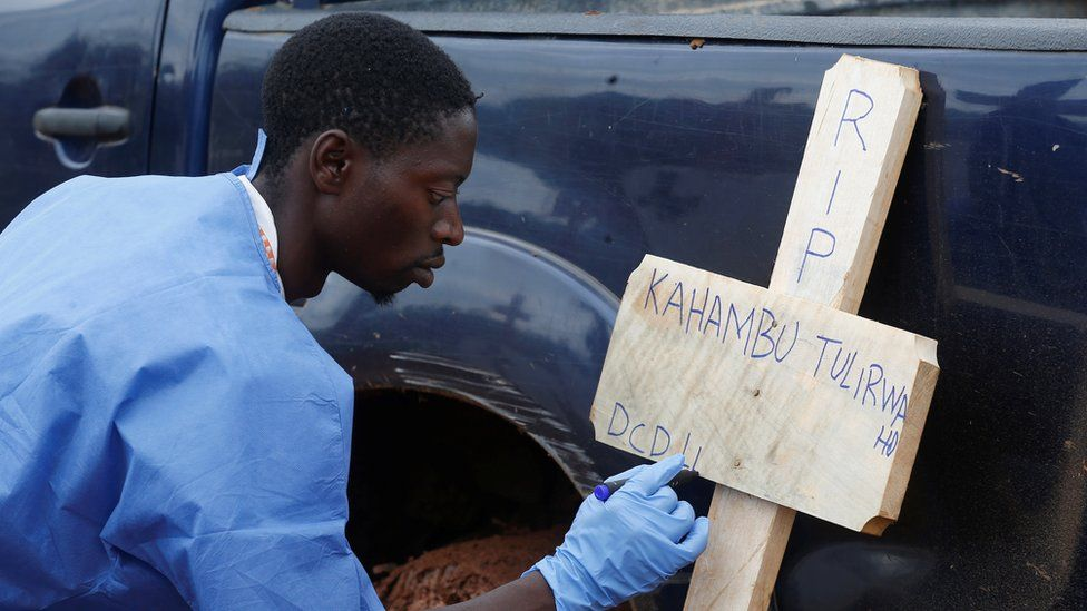 A health worker writes the name of an Ebola victim on a cross