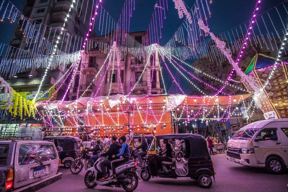 Vehicles drive past a shopped draped in multicoloured neon lights.