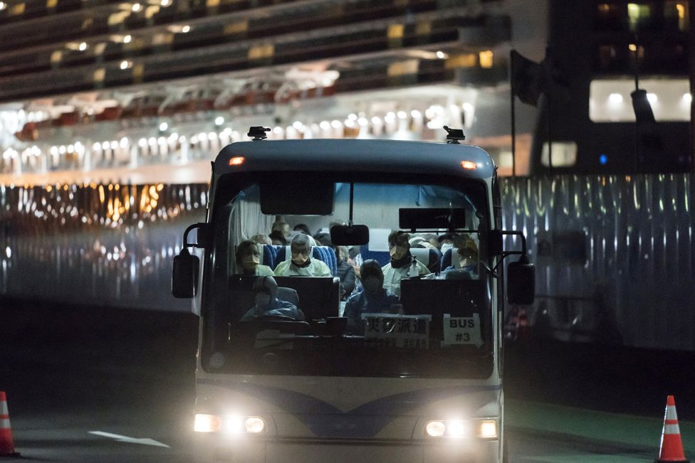 A bus carrying passengers, who will board the Qantas aircraft chartered by the Australian government, from the quarantined Diamond Princess cruise ship drive near Daikoku Pier on 19 February 2020 in Yokohama, Japan.