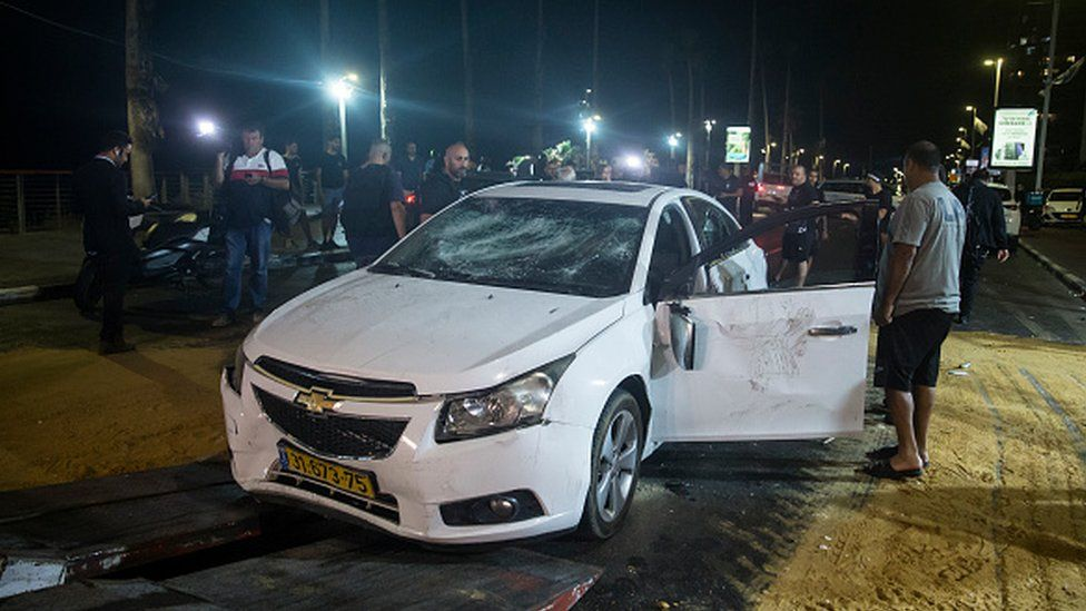 An Israeli man inspects the car of a man who was attacked and injured by a mob in Bat Yam
