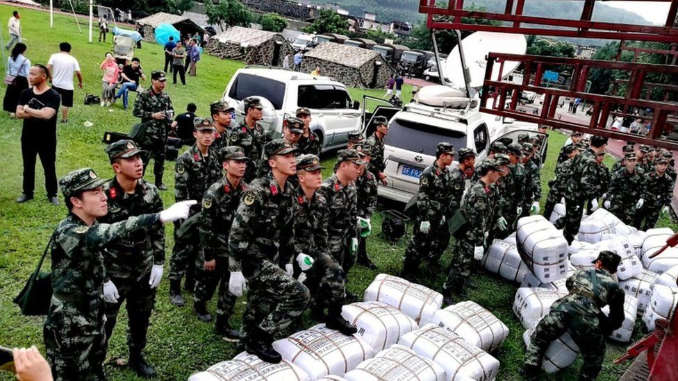 Paramilitary police unload disaster relief packages from a truck at a temporary settlement after the earthquake in Changning county, Sichuan province, China, 18 June 2019
