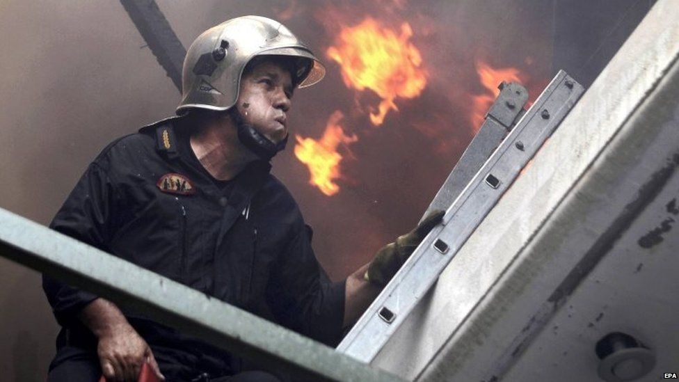 A fireman tries to extinguish a fire in Karea, suburb of Athens, Greece, 17 July 2015.