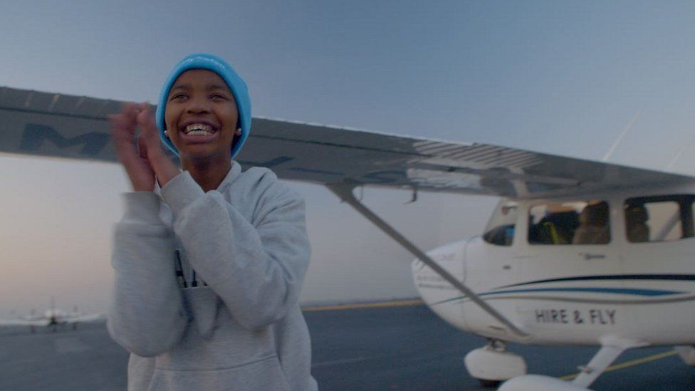 Paballo (Pabi) Leqhotsa standing outside a small plane