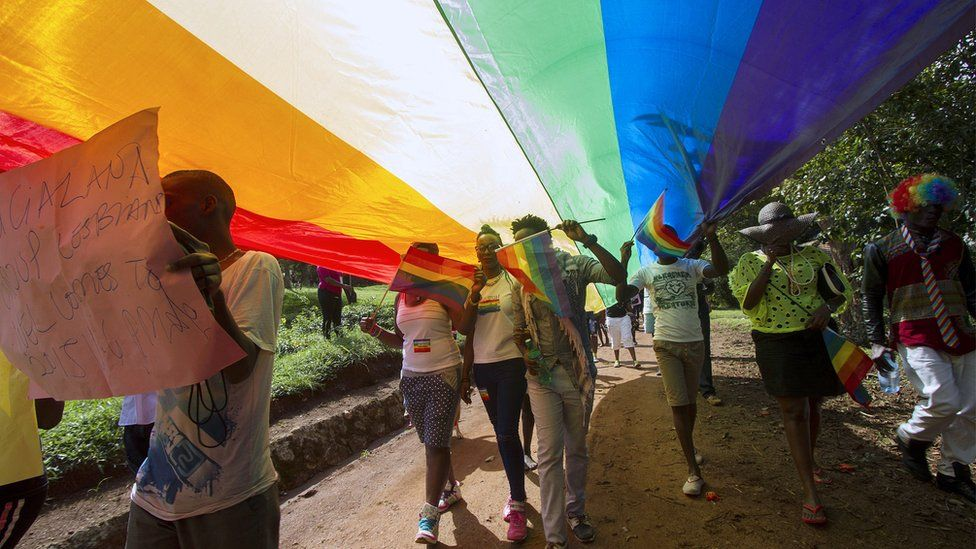 People walk under a giant rainbow flag as they take part in the Gay Pride parade in Entebbe on 8 August 2015.