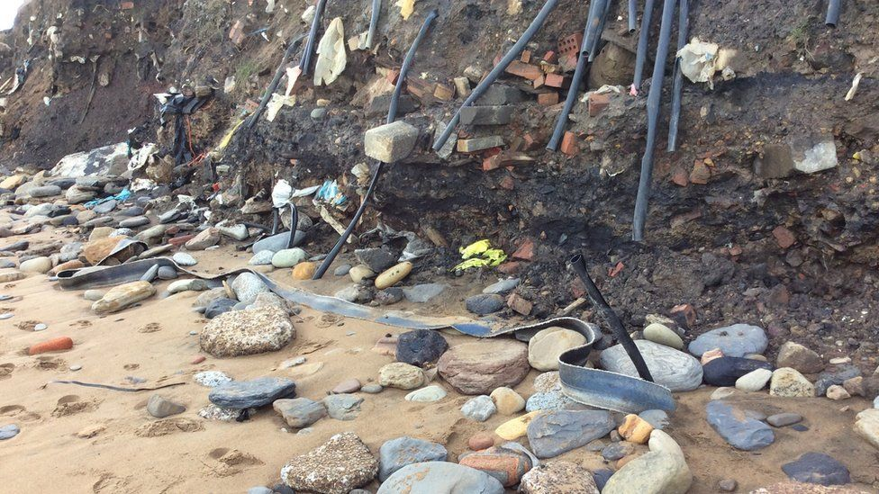 Pipes, cables and other items of rubbish poking through the eroded cliff