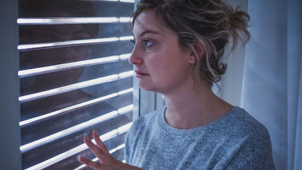 A stock image of a woman standing at a window