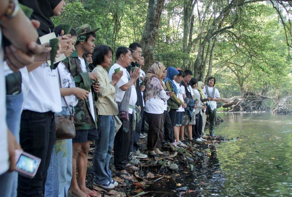 People pray at a riverside memorial service for lost elephants