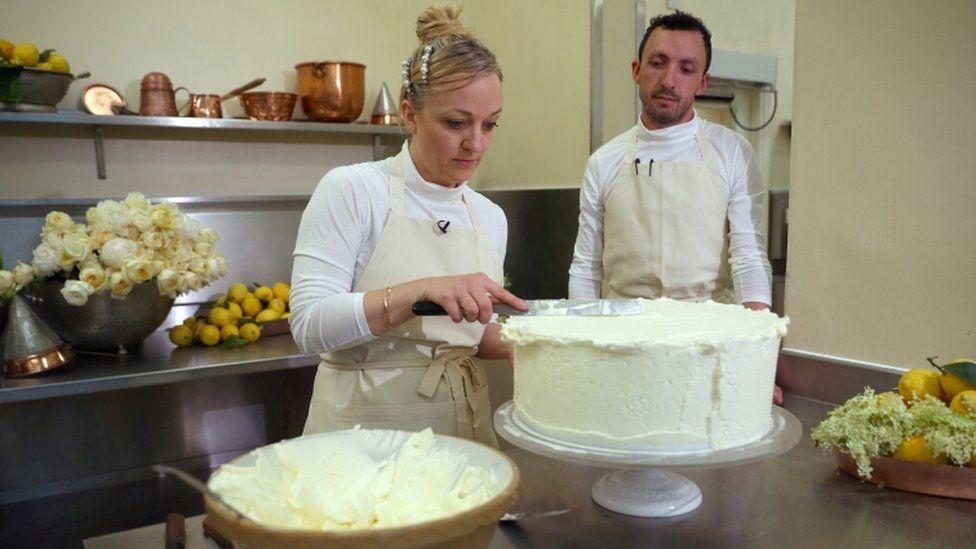 Claire Ptak and Izaak Adams icing the royal wedding cake